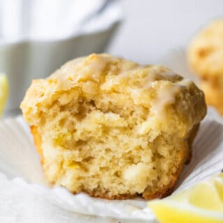 Horizontal image of baked lemon muffin with a bite missing showing fluffy texture. Lemon wedges on the side and a bowl of icing behind the muffin.