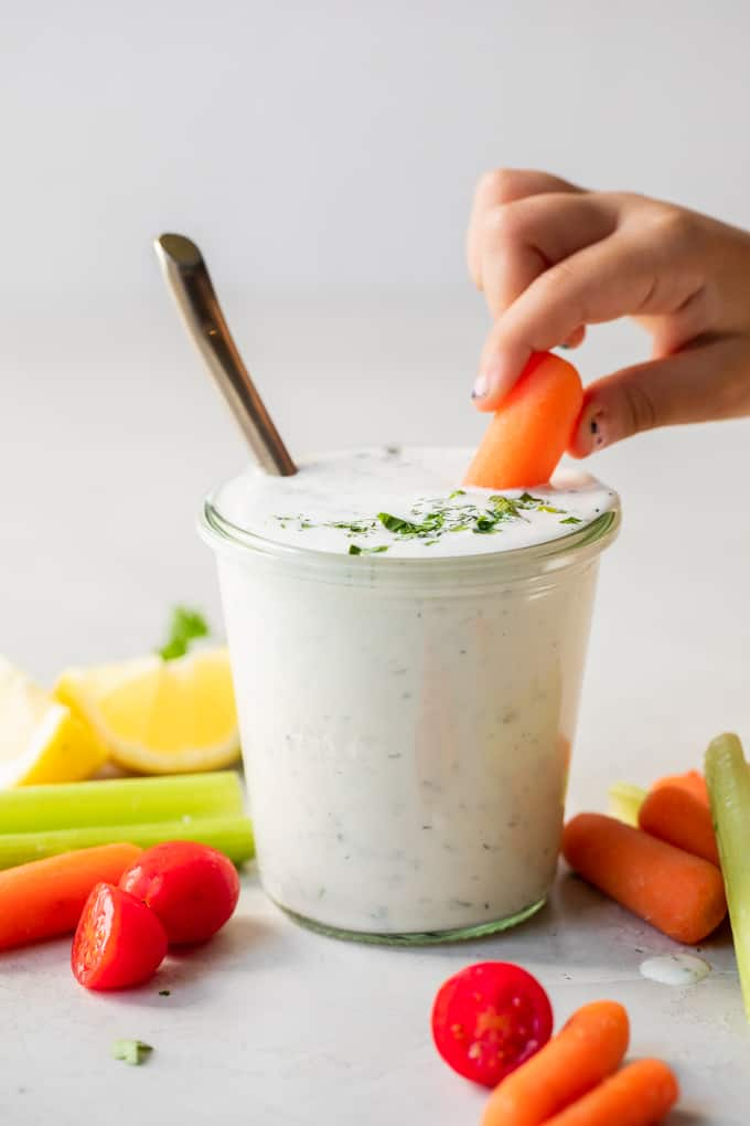 Small hand with chipped nail polish dipping a baby carrot into a jar filled with homemade ranch dressing.
