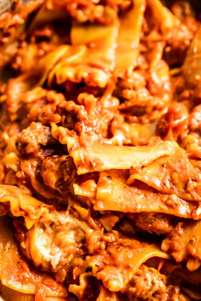 Up close look at lasagna noodles smothered in sauce and coated with melted cheese.