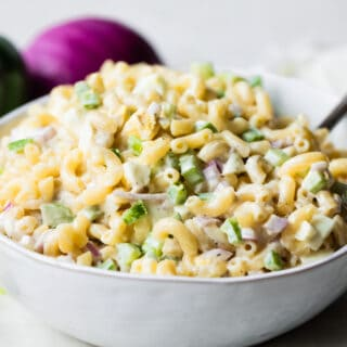 White bowl filled with macaroni salad with a lemon wedge on the side, green bell pepper and red onion in the background.
