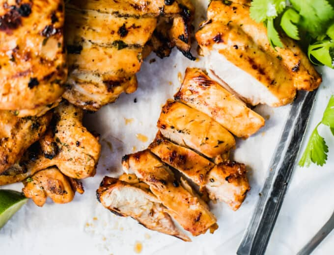 Sliced Mexican grilled chicken on a cutting board with parchment paper, cilantro and a knife.