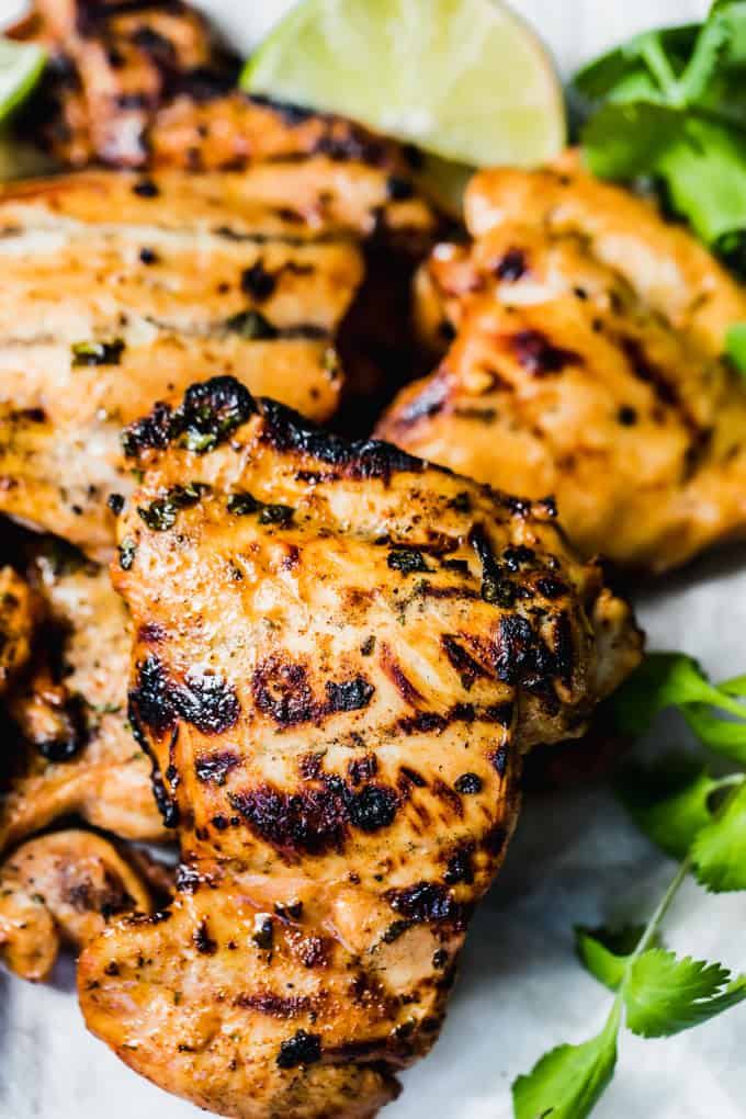 Pile of grilled chicken breast with a sprinkle of cilantro on the side and lime wedges.
