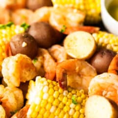 Up close horizontal image of cooked shrimp boil with chunks of corn on the cob, potatoes and shrimp garnished with bits of parsley.