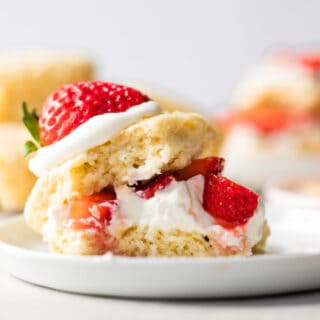 Strawberry shortcake made with a sweet shortcake biscuit, layers of biscuit, whipped cream and strawberries served on a white plate.