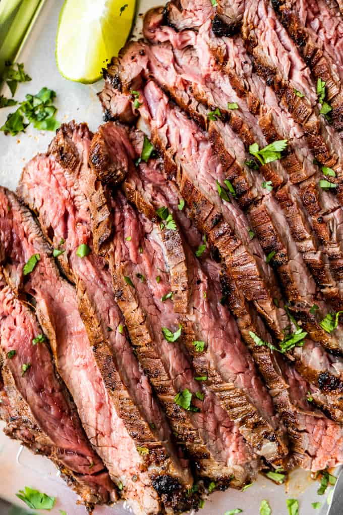 Overhead view of flank steak that has been marinated in carne asada marinade, and grilled. Sliced and laid out on a baking sheet. Topped with bits of green diced cilantro and a lime wedge on the side.