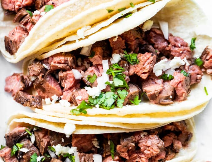 Carne Asada tacos lined up and topped with diced onion, cilantro and crumbled queso fresco. Lime wedges on the side.