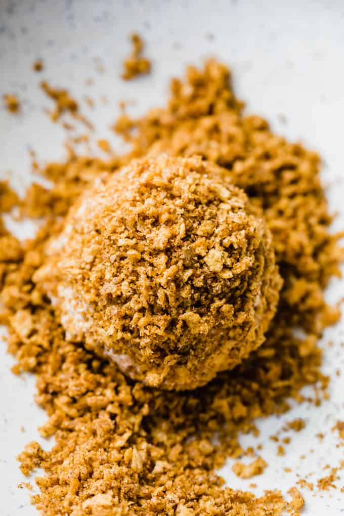 Scoop of ice cream with cinnamon coating being added.