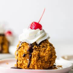 Easy to make mexican fried ice cream on a pink plate topped with drizzles of chocolate fudge, whipped cream and a cherry on top.