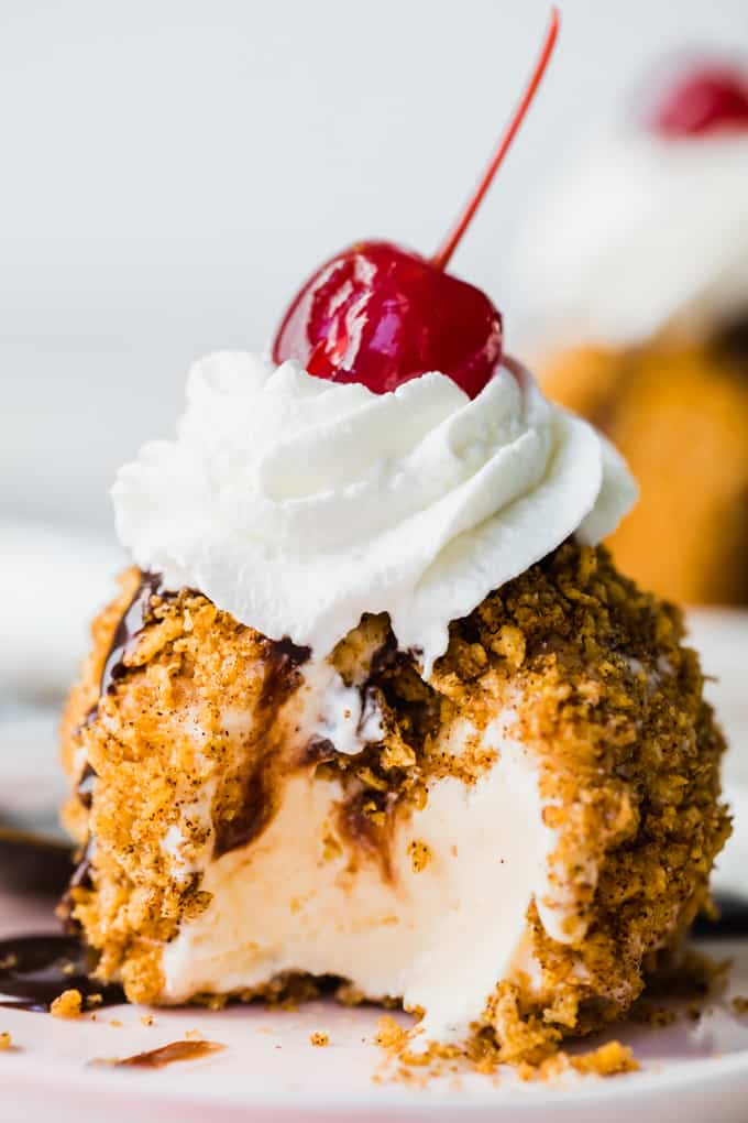 Fried Ice cream with a scoop missing showing creamy ice cream with cinnamon sugar and crunchy coating.
