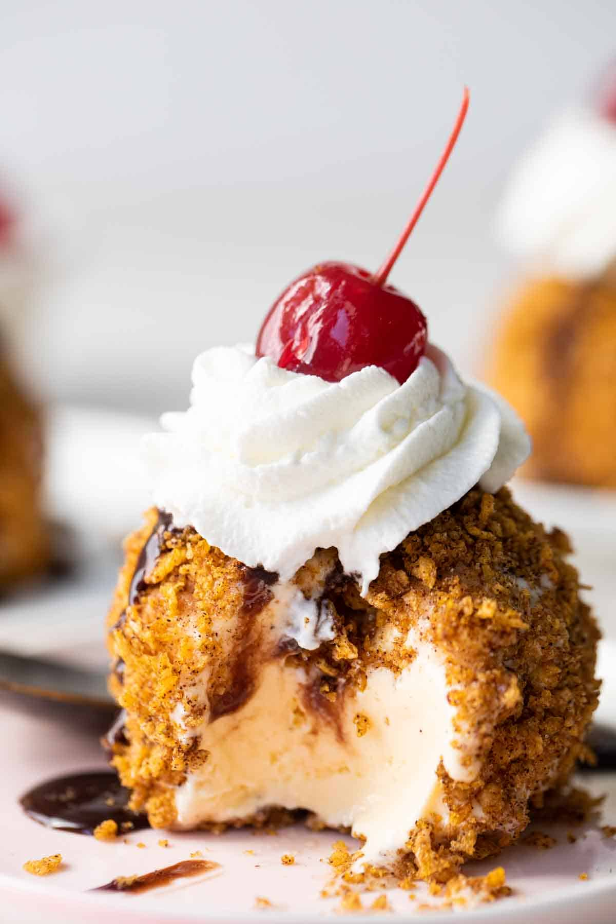 Mexican Fried Ice Cream topped with whipped cream and a cherry with a bite taken out on a plate.