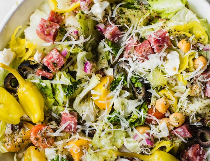 Italian chop salad, lettuce with diced salami, tomatoes, chick peas, tomatoes, red onion, and more all drizzled with Italian dressing, topped with whole pepperoncinis.