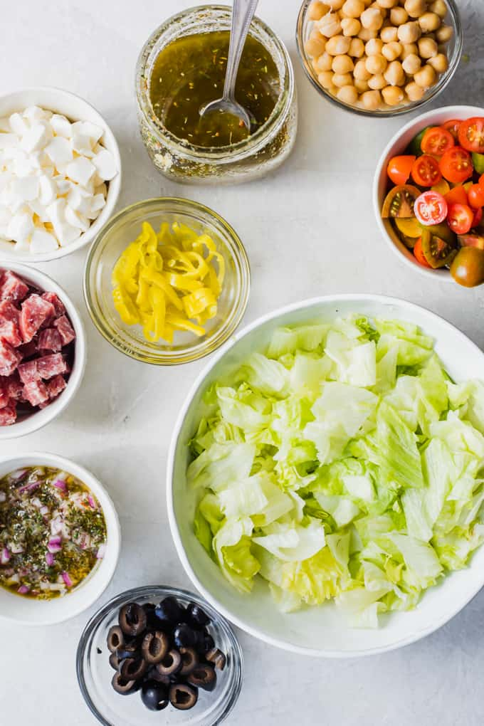 Ingredients laid out for an Italian Chop salad. A large bowl of chopped lettuce, salami, olives, tomatoes, chick peas, mozzarella, pepperoncinis, red onion, and a jar of homemade Italian dressing.
