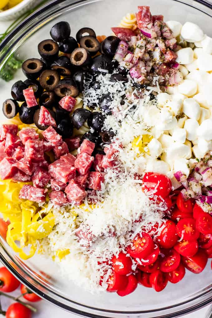 Overhead view of ingredients for Italian pasta salad in a glass bowl.