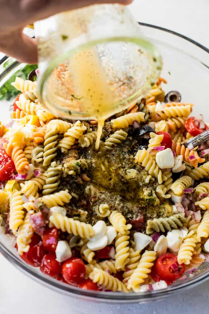 Italian dressing being poured over the top of pasta salad.