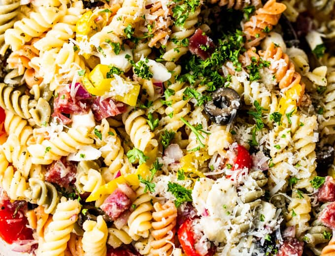 Close up view of rotini noodles with tomatoes, olives, salami, mozzarella, pepperoncinis, and shredded parmesan and fresh parsley, coated in Italian dressing.