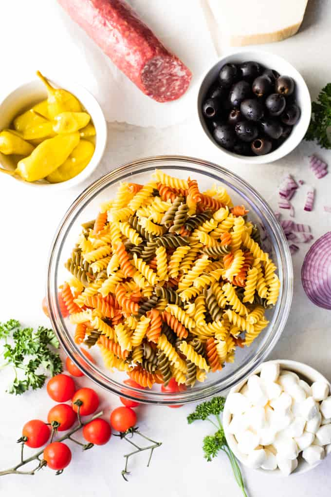 Overhead view of showing a bowl of rotini noodles, bowls of olives, mozzarella, pepperoncini, red onion, cherry tomatoes, and fresh parsley.