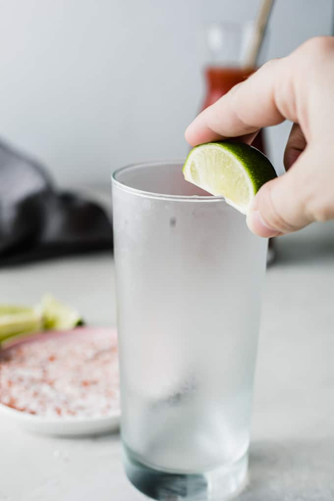 Lime being rubbed on the rim of the glass.
