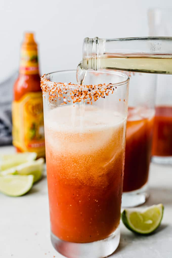 Frosty mug with Tajin on the rim filled with ice and tomato juice, with a beer being poured in.