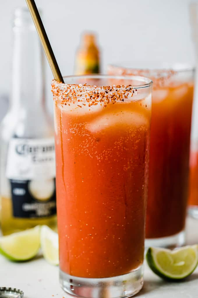 Glass filled with red Michelada drink, showing ice cubes, Tajin on the rim of the cup, lime wedges on the counter, and a corona bottle behind the glasses.