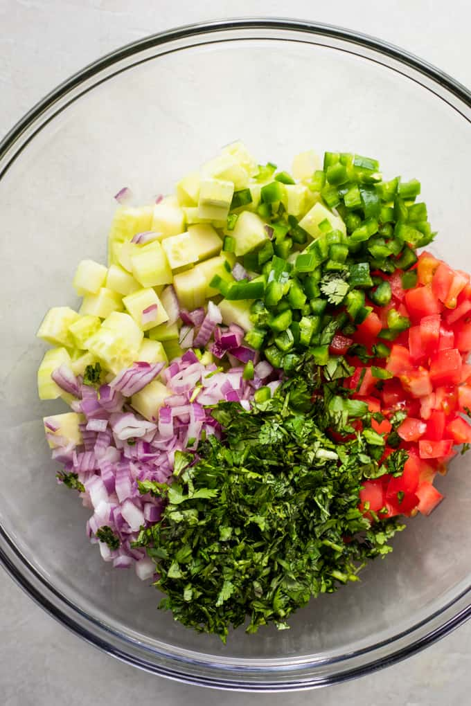 Glass bowl filled with diced cucumber, red onion, jalapeño, tomato, and cilantro.