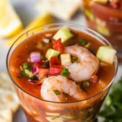 Small cocktail glass filled with Mexican shrimp cocktail, showing shrimp, tomatoes, avocado, red onion, and cucumber swimming in a red spiced juice.
