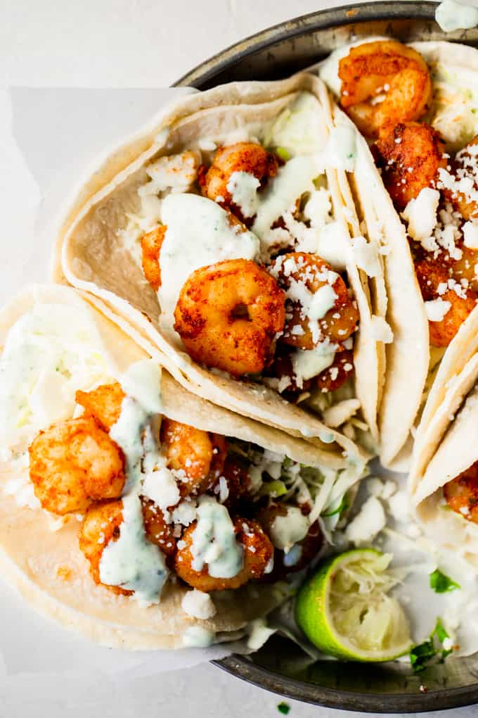 Corn tortillas filled with cabbage and taco seasoned shrimp. Topped with crumbled queso fresco and lime Crema. Lime wedges on the side.