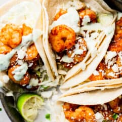 Tray filled with shrimp tacos that are topped with crumbled queso fresco, and drizzled with a cilantro lime Crema.