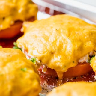 Slice of tomato topped with tuna salad and covered with melted cheese.