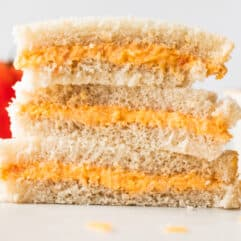 Stack of tomato twiddle sandwiches on white bread, with grated cheese on the counter around them, a tomato in the background and a ramekin filled with tomato twiddle.