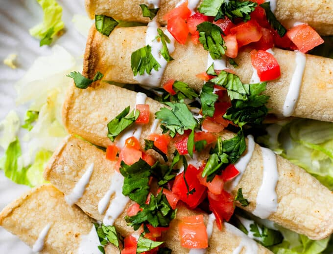 A plate filled with baked chicken taquitos, topped with drizzles of Crema, diced tomato, and fresh cilantro.