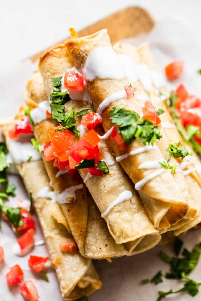 Overhead view of stacked taquitos drizzled with Crema, diced tomato and cilantro.
