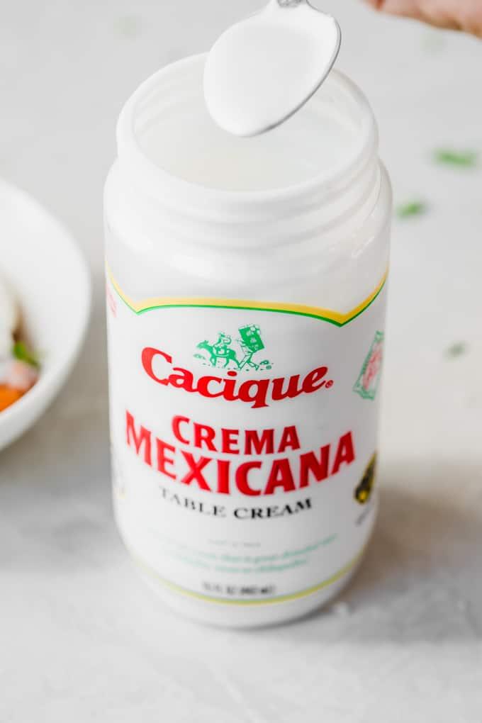 Spoon dipping into a jar of Cacique Crema Mexicana.