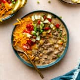 Bowl filled with cheeseburger soup and topped with diced tomatoes, pickles, cheese and herbs.
