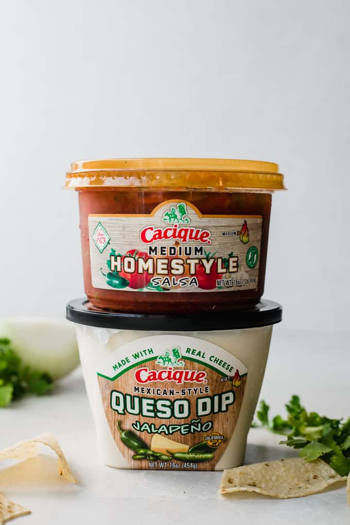 Stacked containers of Cacique brand Medium Homestyle Salsa and Mexican Style Queso Dip Jalapeno.