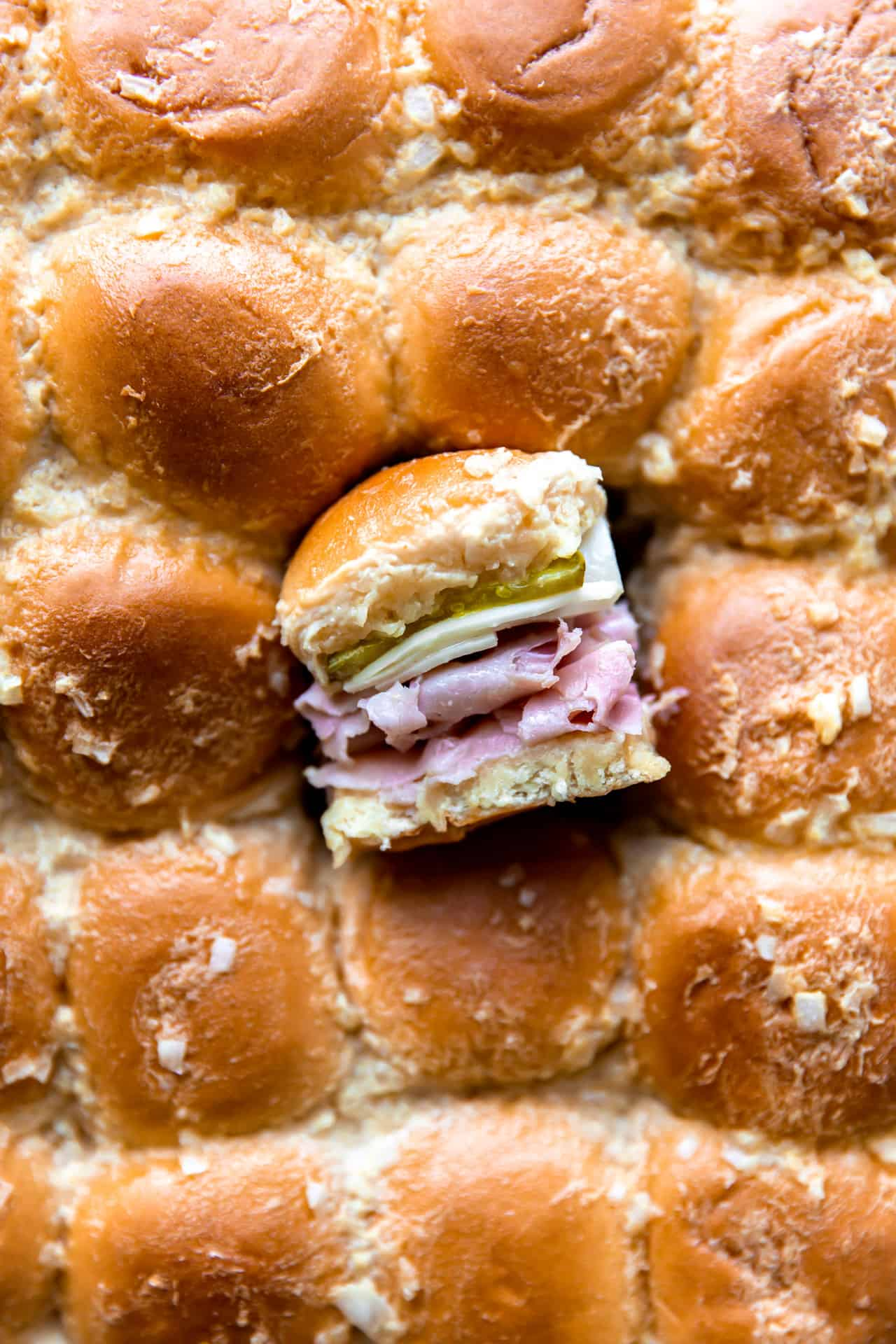 Overhead shot of the tops of sliders with one slider cut out and turned on it's side to show the layers of buns, sliced ham, Swiss cheese and pickles on the inside.