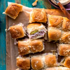 Overhead shot of a tray of cuban sliders that have been sliced apart, showing stretchy melty cheese attaching them.