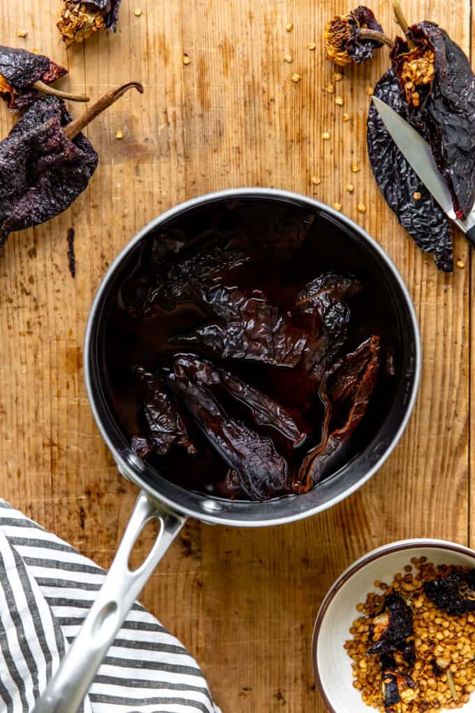 Dried chilis that have been de-seeded and toasted soaking in water in a saucepan.
