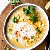 Bowl serving of Mexican Corn Chowder topped with Crema and crumbled queso fresco.