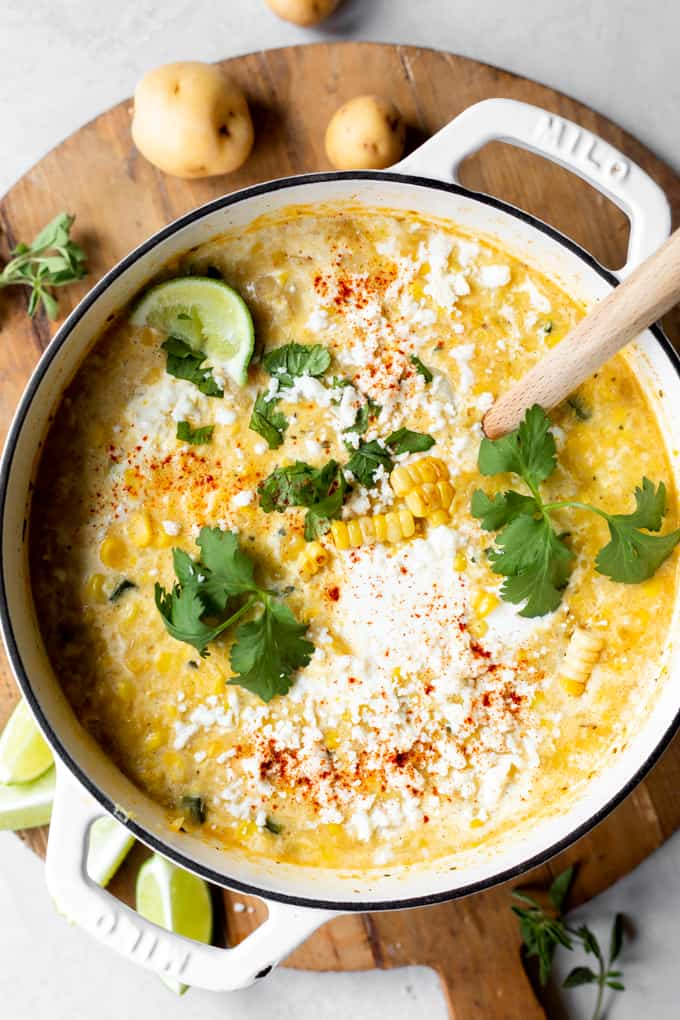 Pot filled with Mexican street corn chowder topped with Crema, queso fresco, and fresh cilantro.