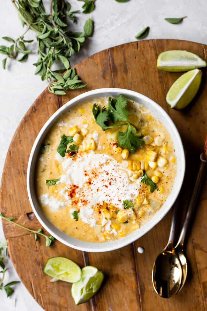 Bowl of Mexican Street Corn Chowder served with a swirl of Crema and crumbled queso fresco, lime wedges on the side.