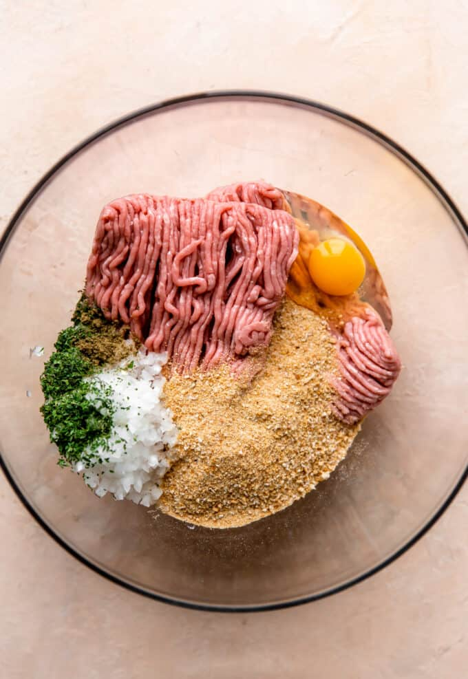 Ingredients for turkey meatballs in a glass bowl, ground turkey, bread crumbs, diced onion, egg and herbs and seasonings.
