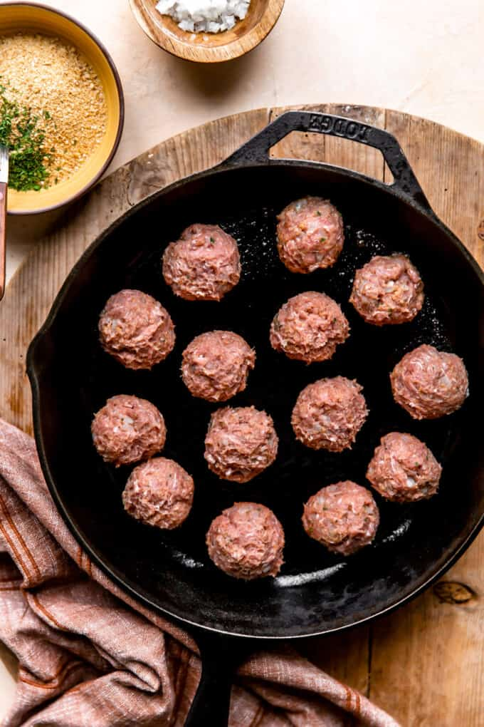 Turkey meatballs in a large cast iron skillet for cooking.