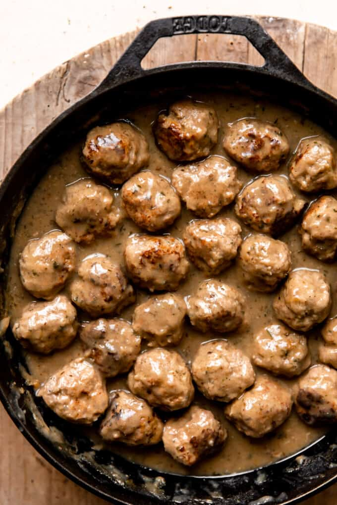 Cooked turkey meatballs in a large cast iron skillet simmering in creamy gravy.