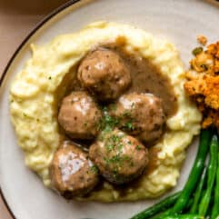 Turkey meatballs and gravy served over mashed potatoes on a plate with green beans and stuffing on the side.