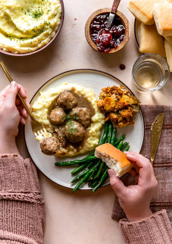 Hands around a plate of turkey meatballs served over mashed potatoes, bread rolls, green beans and stuffing.