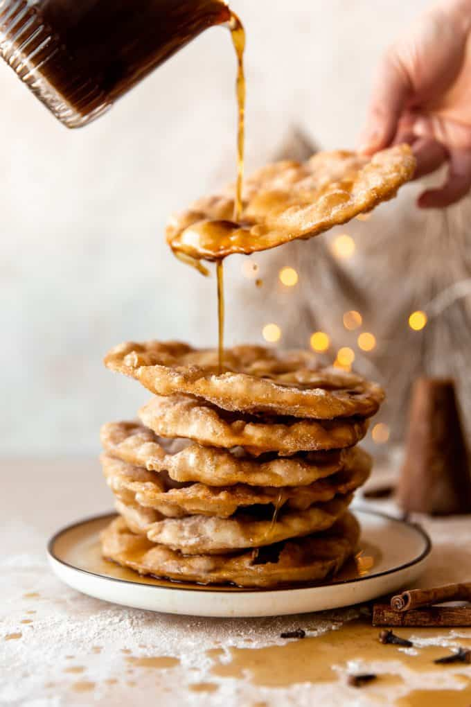 Piloncillo syrup drizzling over a stack of freshly fried bunuelos.