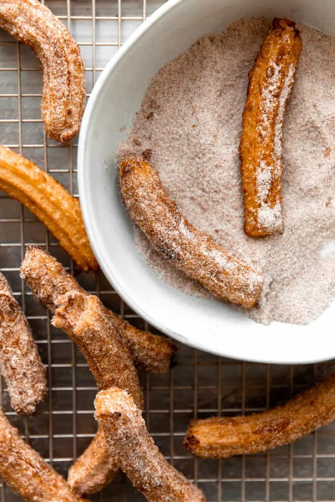 Fried churros being coated in cinnamon sugar mixture.