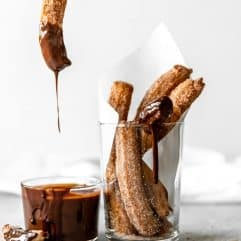 Churro being dipped into chocolate fudge.
