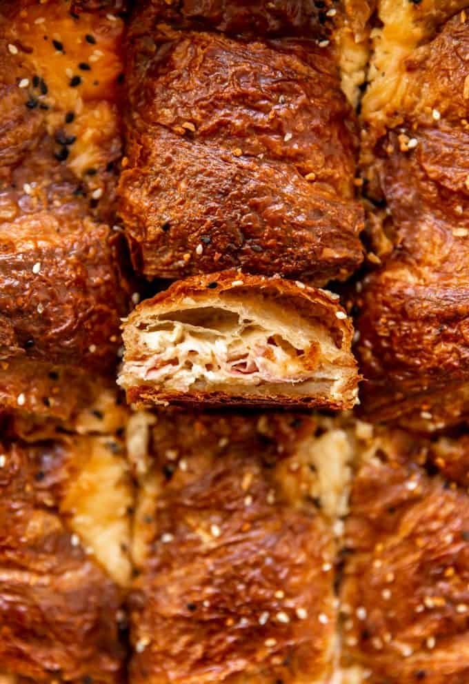 Croissant that has been cut showing flakey layers filled with melted provolone and layers of ham baked with egg custard for a breakfast casserole.
