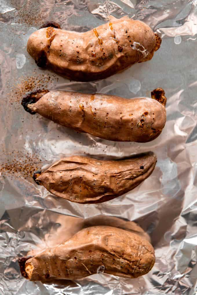 Sweet potatoes on a baking sheet lined with foil and holes piercing the skin.